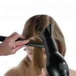 """Step 3 - Cominciare con la parte più larga della sezione spruzzando uno spray termico e modellando i capelli a forma a """"C"""". Bloccare le lunghezze con un pettine e asciugare completamente il prodotto termico con il phon."""